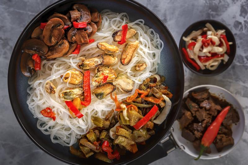 Traditional Asian food - rice noodles with seafood, salad, red pepper and fried mushrooms are on a gray table. royalty free stock photography