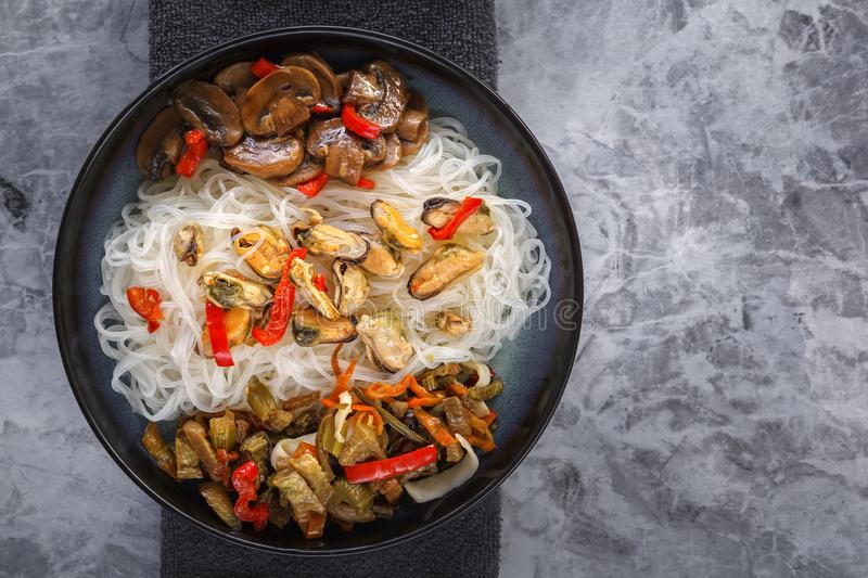 Traditional Asian food - rice noodles with seafood, salad, red pepper and fried mushrooms are on the side table. stock photos