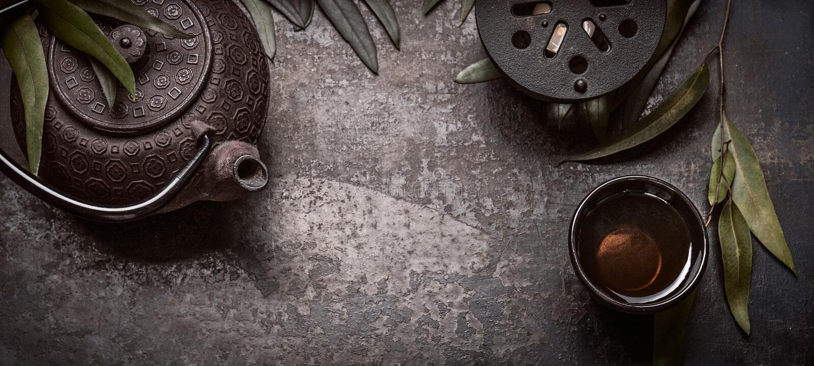 Traditional Asian green tea set with teapot and cups and candle on dark rustic background with copy space, banner or template, top. View stock images