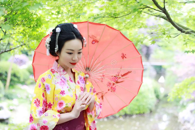 Traditional Asian Japanese beautiful Geisha woman bride wears kimono hold a red umbrella in a summer nature stock image