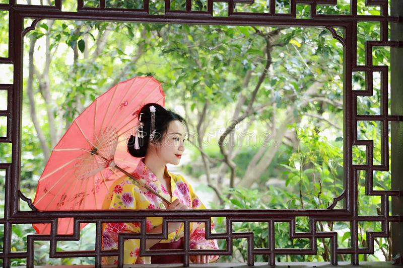 Traditional Asian Japanese beautiful Geisha woman bride wears kimono with red umbrella on hand in a summer nature royalty free stock photos