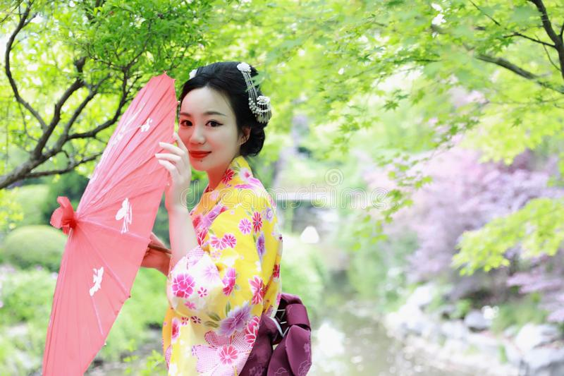 Traditional Asian Japanese beautiful Geisha woman wears kimono bride with a red umbrella in a graden. Japanese woman with kimono Japanese bride smiling stand by royalty free stock photo