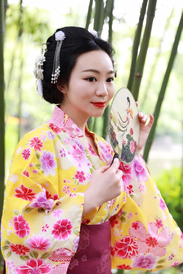 Traditional Asian Japanese beautiful Geisha woman wears kimono hold a fan on hand in a summer graden. Japanese woman with kimono Japanese bride smiling stand by stock images