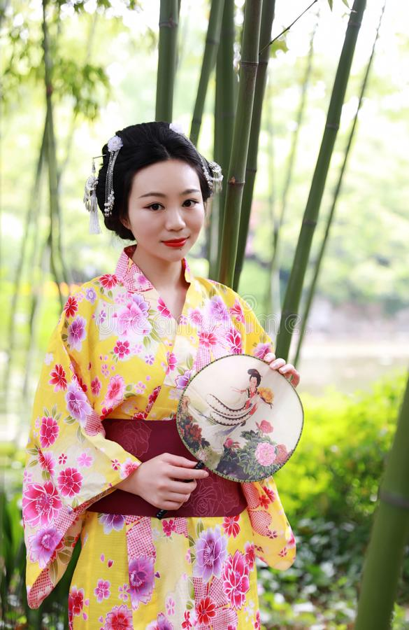 Traditional Asian Japanese beautiful Geisha woman wears kimono hold a fan on hand under a tree in a summer graden. Japanese woman with kimono Japanese bride royalty free stock image