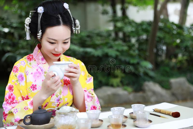 Traditional Asian Japanese beautiful Geisha woman wears kimono show tea art ceremony drink tea in a summer spring outdorr garden. Japanese woman with kimono royalty free stock photos