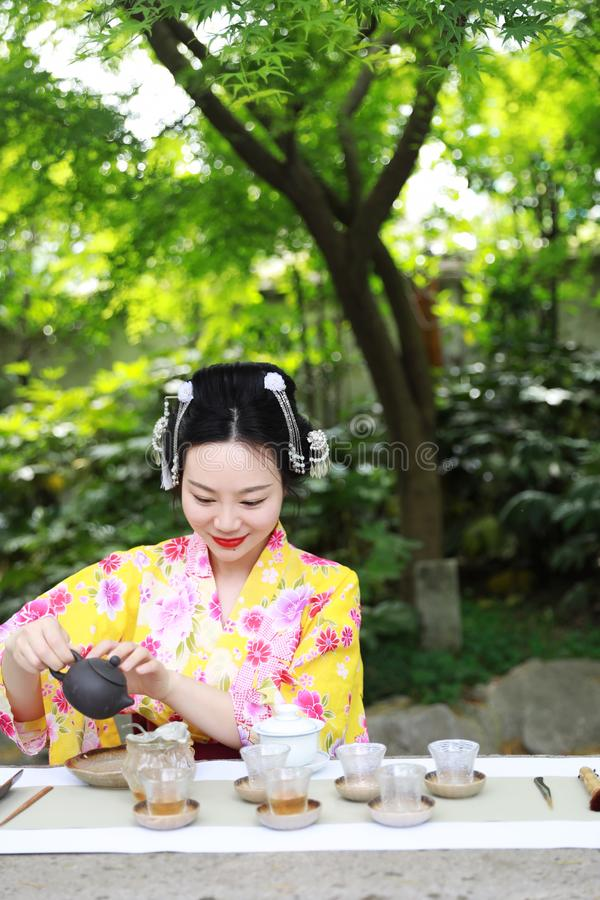 Traditional Asian Japanese beautiful woman conduct tea ceremony. Japanese woman with kimono Japanese bride smiling stand by bamboo in a spring park Geisha with royalty free stock photos