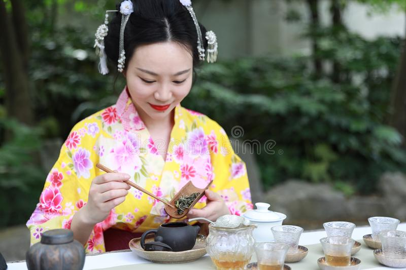 Traditional Asian Japanese beautiful woman conduct tea ceremony in outdoor garden. Japanese woman with kimono Japanese bride smiling stand by bamboo in a spring royalty free stock image