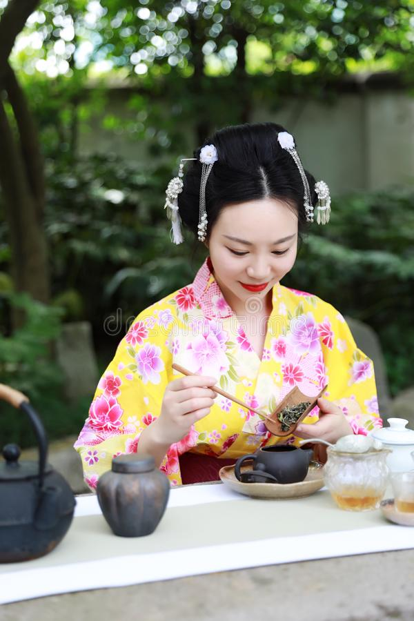Traditional Asian Japanese beautiful woman show tea art green tea ceremony in outdoor garden. Japanese woman with kimono Japanese bride smiling stand by bamboo stock image
