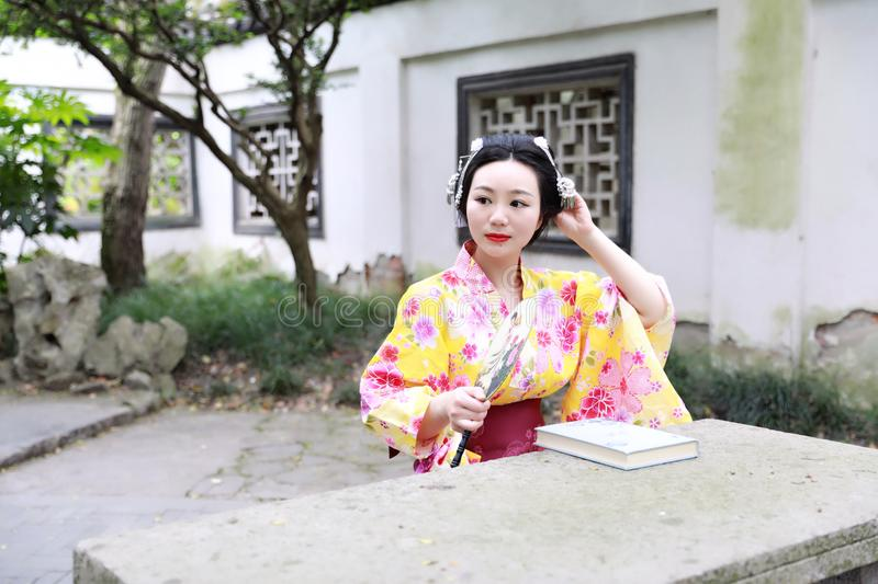 Traditional Asian Japanese beautiful woman wears kimono with fan on hand reading book in outdoor spring garden. Japanese woman with kimono Japanese bride smiling stock images