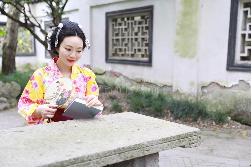 Traditional Asian Japanese beautiful woman wears kimono with fan on hand reading book in outdoor spring garden. Japanese woman with kimono Japanese bride smiling royalty free stock image