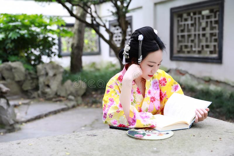 Traditional Asian Japanese beautiful woman wears kimono with fan on hand reading book in outdoor spring garden. Japanese woman with kimono Japanese bride smiling royalty free stock photography