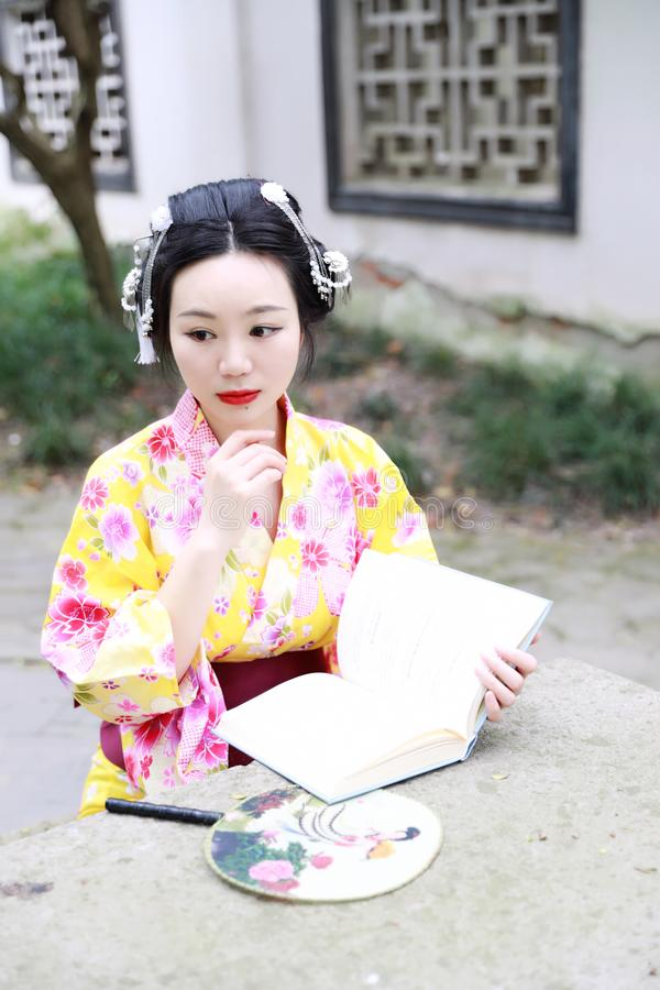 Traditional Asian Japanese beautiful woman wears kimono with fan on hand reading book in outdoor spring garden. Japanese woman with kimono Japanese bride smiling royalty free stock photo