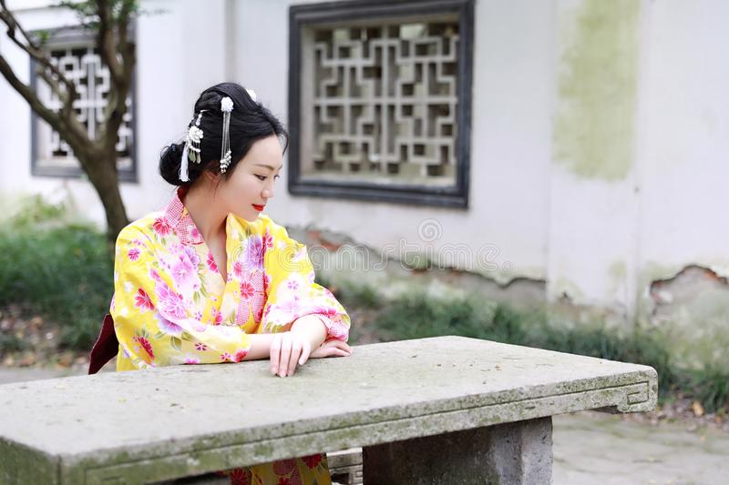 Traditional Asian Japanese beautiful woman wears kimono sit on stone bench in outdoor spring garden. Japanese woman with kimono Japanese bride smiling stand by stock photos