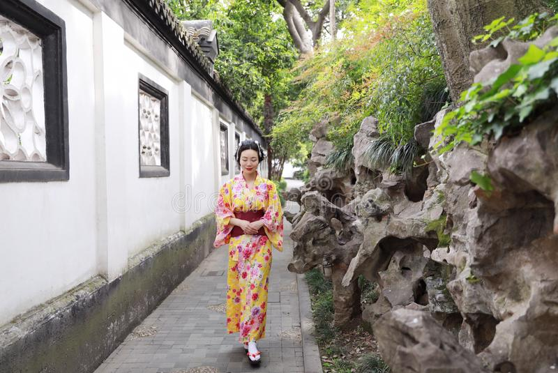 Traditional Asian Japanese beautiful woman wears kimono in a spring garden park stand by bamboo enjoy free time. Japanese woman with kimono Japanese bride royalty free stock photos