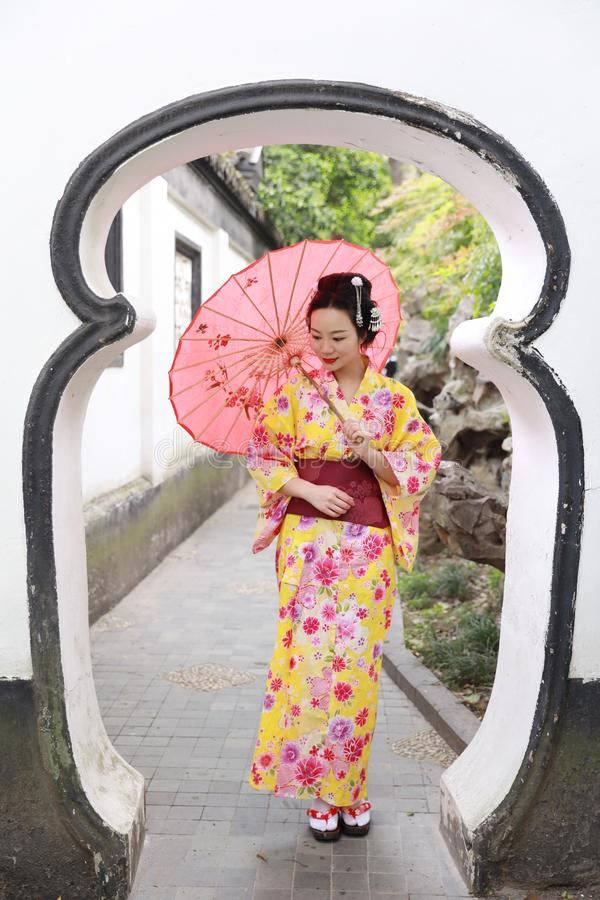 Traditional Asian Japanese beautiful woman wears kimono in a spring garden park stand by bamboo enjoy free time fan umbrella. Japanese woman with kimono Japanese royalty free stock image