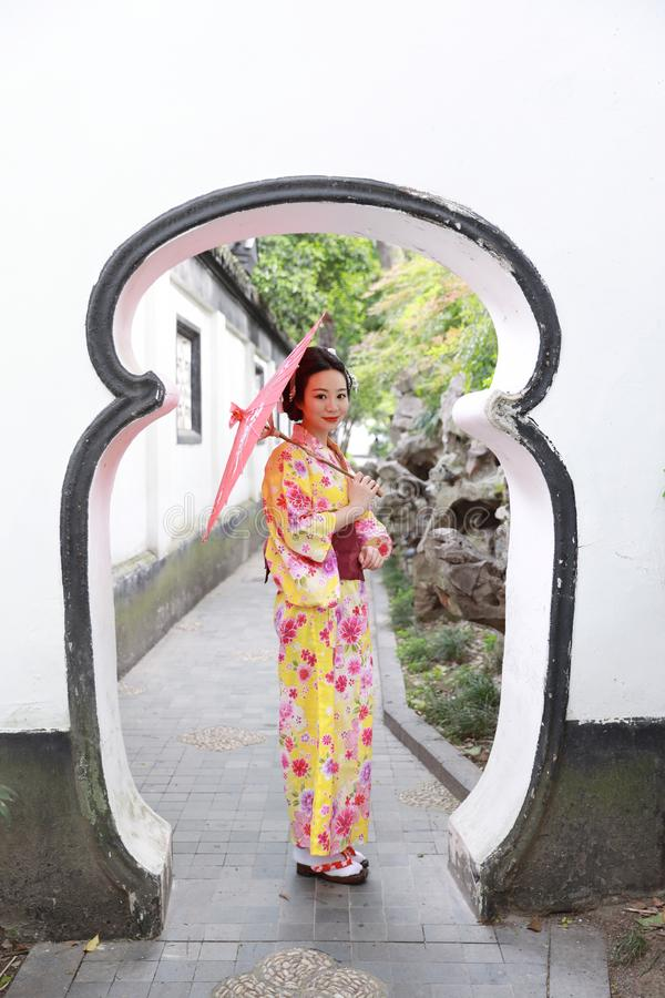 Traditional Asian Japanese beautiful woman wears kimono in a spring garden park stand by bamboo enjoy free time fan umbrella. Japanese woman with kimono Japanese stock photos