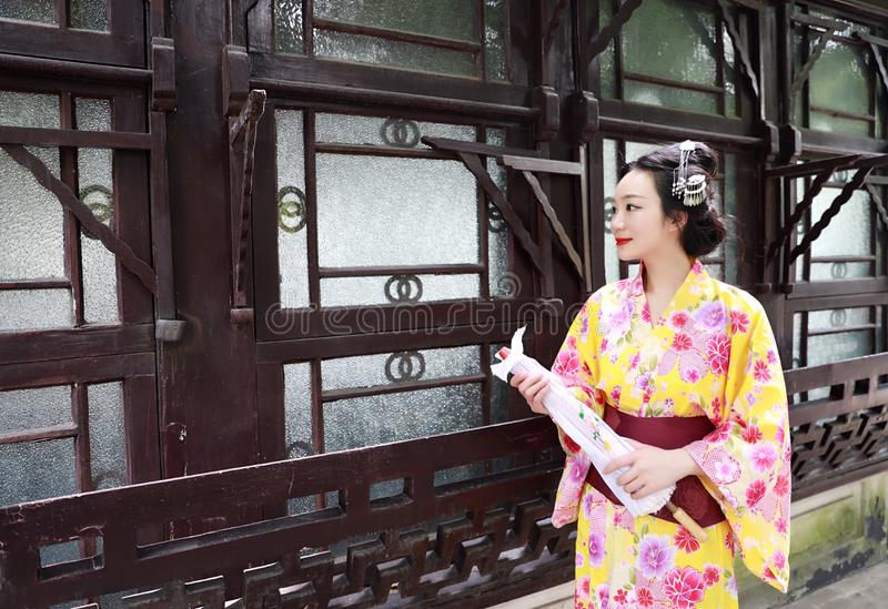 Traditional Asian Japanese woman bride Geisha wearing kimono play in a graden hold an umbrella stand by a boat. Japanese woman with kimono Japanese bride smiling royalty free stock images