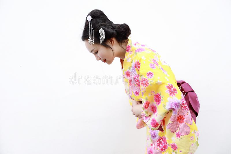 Traditional Asian Japanese woman with kimono respectful bow on isolated white background. Japanese woman with kimono Japanese bride smiling stand by bamboo in a stock photography