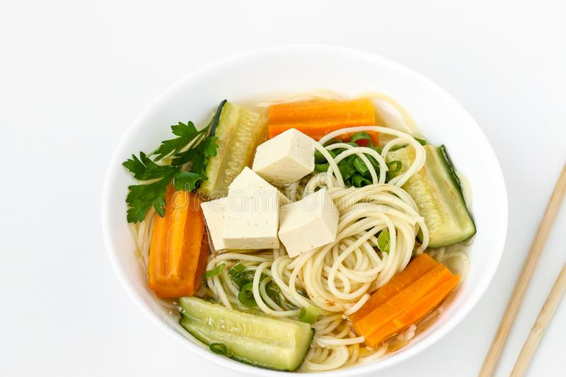 Traditional asian soup with tofu cheese, noodles, carrots and zucchini on white background. This dish usually contains bouillon royalty free stock photos