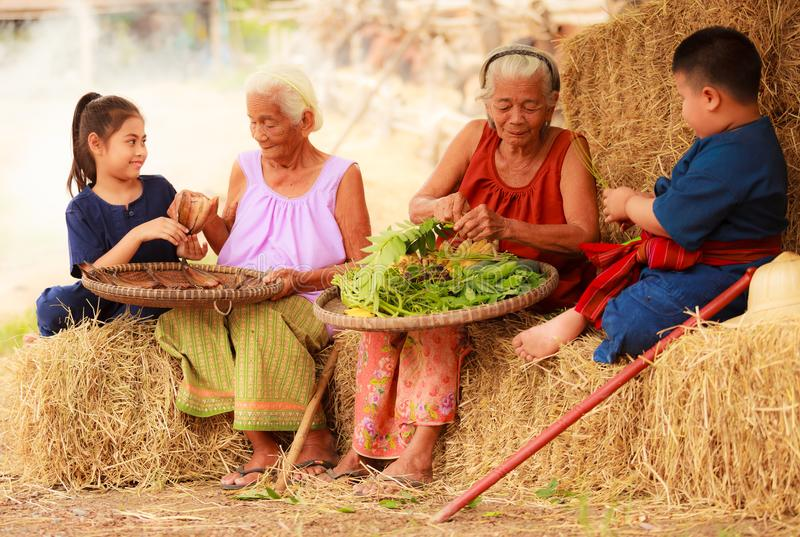 Traditional Asian Thai rural daily life, grandchildren in cultural costumes help their seniors preparing local food ingredients stock image