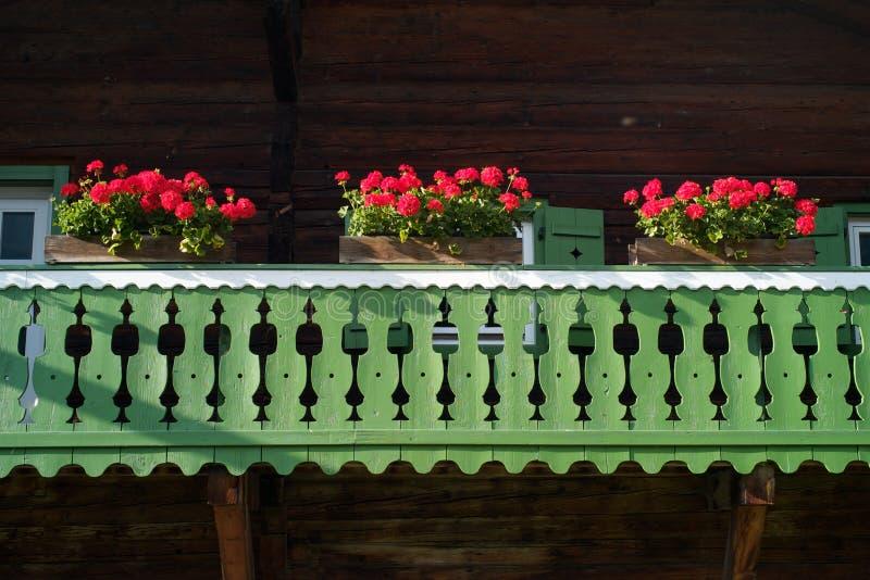 Traditional Austrian Balcony with Ref Flowers. A Traditional Balcony with Red Flowers of a Wood House in Salzburg, Austria stock photo
