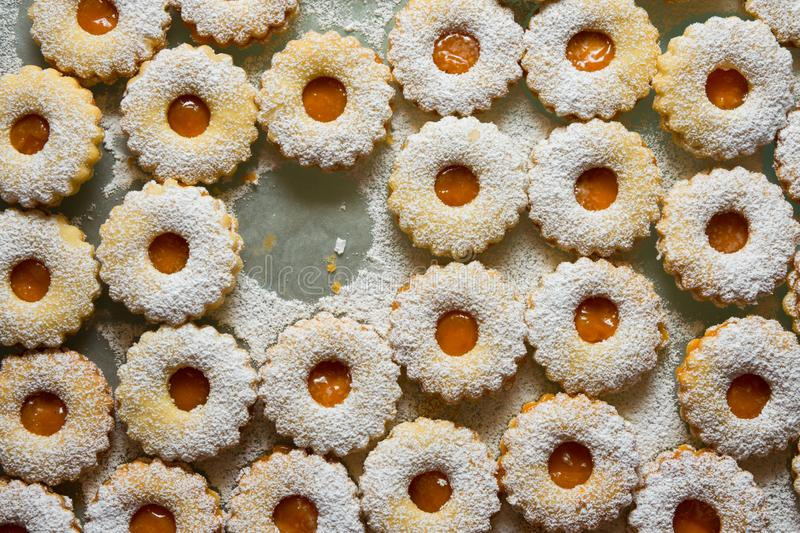 Traditional Austrian home baked Christmas cookies Linzer eyes with apricot jam powdered on baking tray. Process of preparation royalty free stock photo