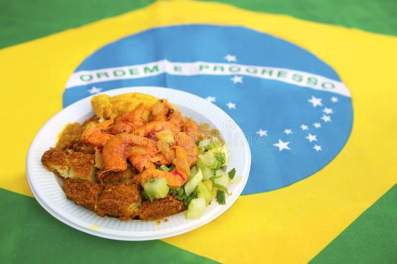 Traditional Authentic Acaraje Salvador Bahia Brazil. Plate of traditional authentic acaraje from a famous stand in Salvador Bahia Brazil on Brazilian flag royalty free stock photo