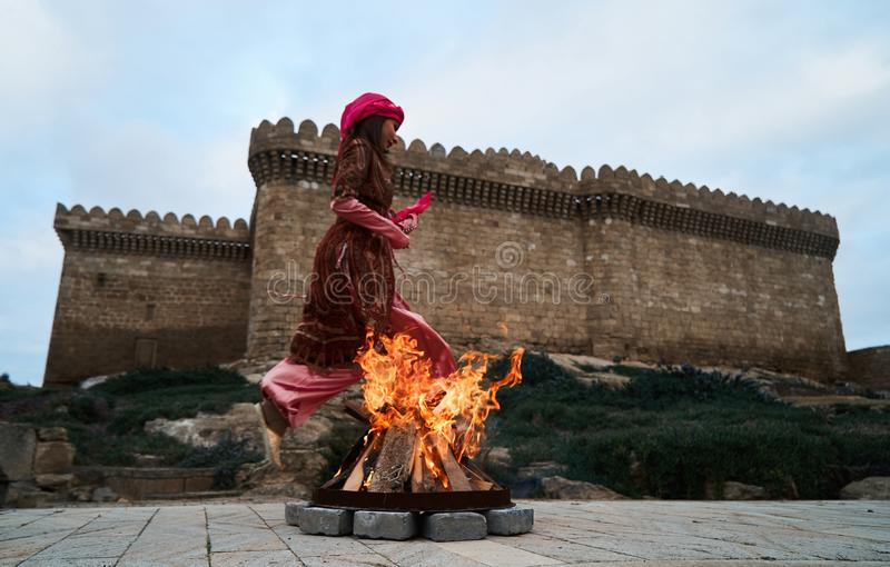 Traditional Azerbaijani Novruz holiday celebration with beautiful girl Jumping over the fire, stock photography