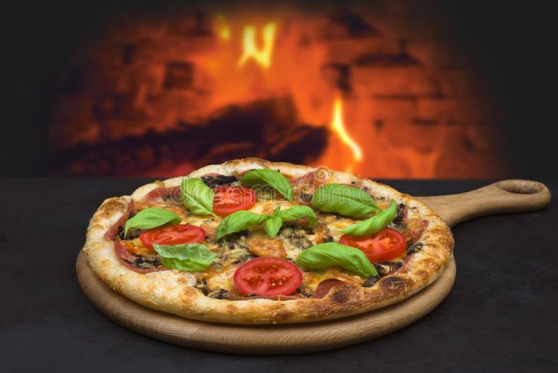 Traditional baked pizza on background of blurred brick oven fire royalty free stock photos