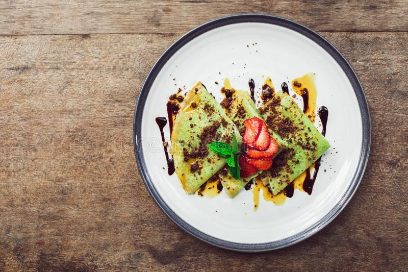 Traditional bali green pancakes with strawberry. Traditional indonesian green pancakes topping with chocolate and strawberries slices. Breakfast food concept stock photo