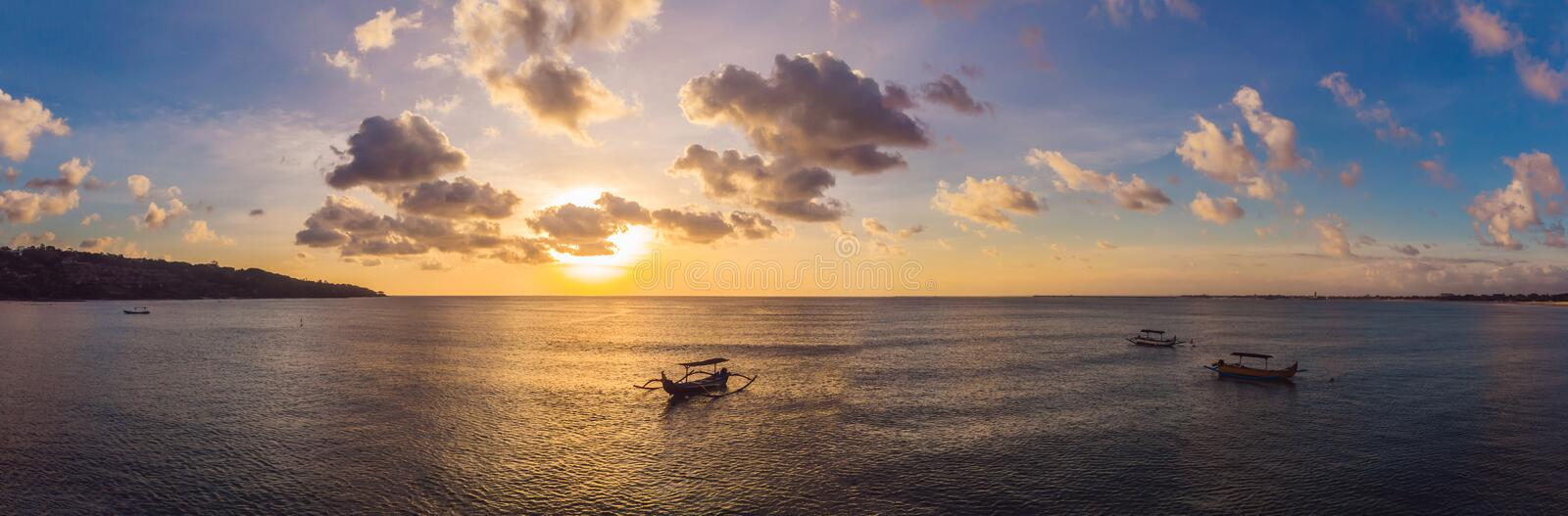 Traditional Balinese boat Jukung at Jimbaran beach at sunset in Bali, Indonesia Photo from the drone. Traditional Balinese boat Jukung at Jimbaran beach at royalty free stock photo