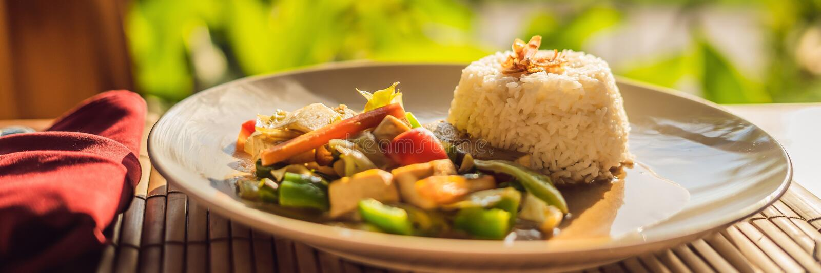 Traditional Balinese cuisine. Vegetable and tofu stir-fry with rice BANNER, long format. Traditional Balinese cuisine. Vegetable and tofu stir-fry with rice stock photo