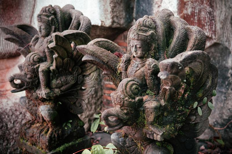 Traditional Balinese guard angel statue carved in dark stone close up stock images