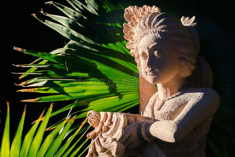 Traditional Balinese sandstone statue of woman, welcome offering in her hand royalty free stock photography
