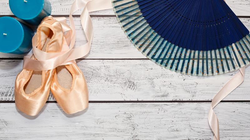 Ballet shoes and show props on wooden stage. Traditional ballet shoes calling pointe with hard metal insole and some dancing show props lie on wooden theater stock image