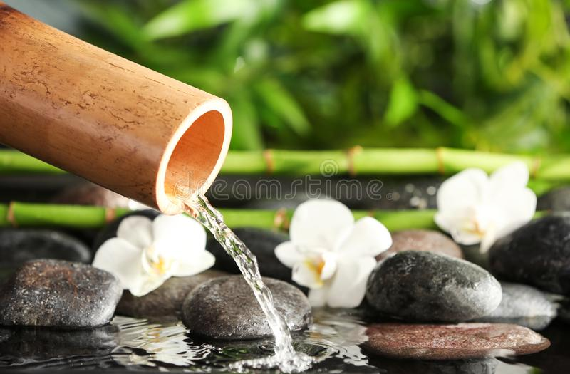 Traditional bamboo fountain with spa stones and flowers, closeup stock photos