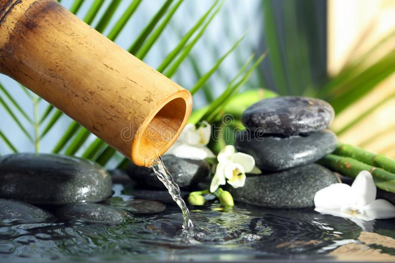 Traditional bamboo fountain with spa stones stock photography