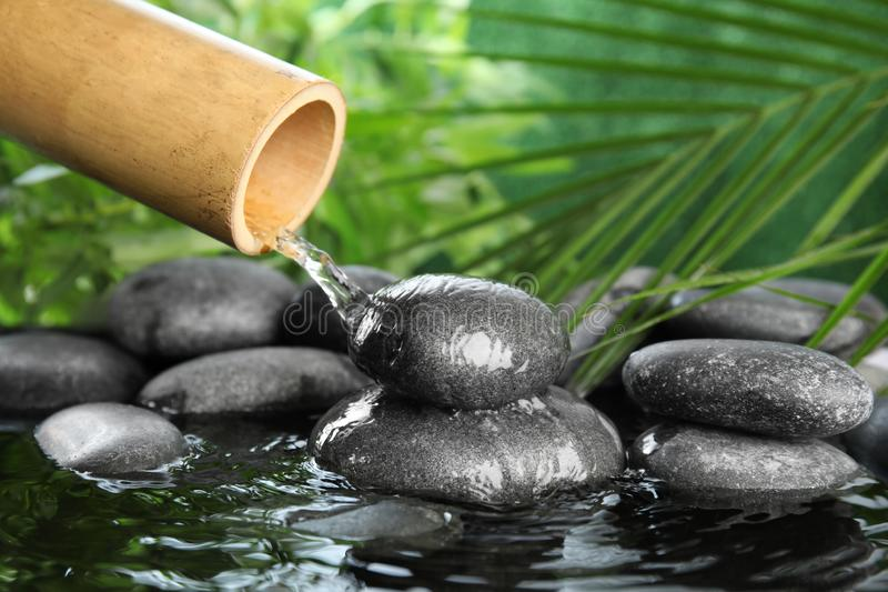 Traditional bamboo fountain with zen stones stock photography