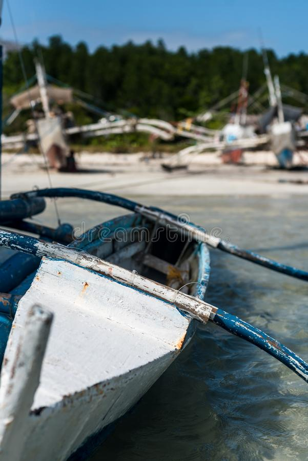 A fishing boat leaning in the shallow water by the beach. A traditional Banca, or fishing boat, in the Phillippines, is leaning in the shallow waters at the stock photography