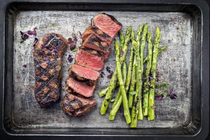 Traditional barbecue dry aged sliced roast beef steak with green asparagus on an old rustic metal tray stock photos