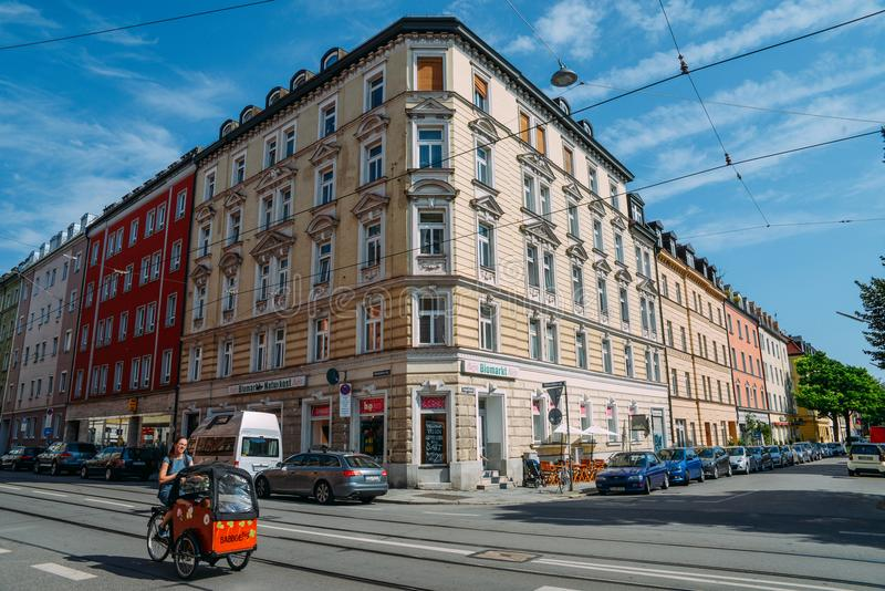Traditional Bavarian architecture in the centre of Munich on a sunny day. Woman cycles in a push cart with her kids stock photo