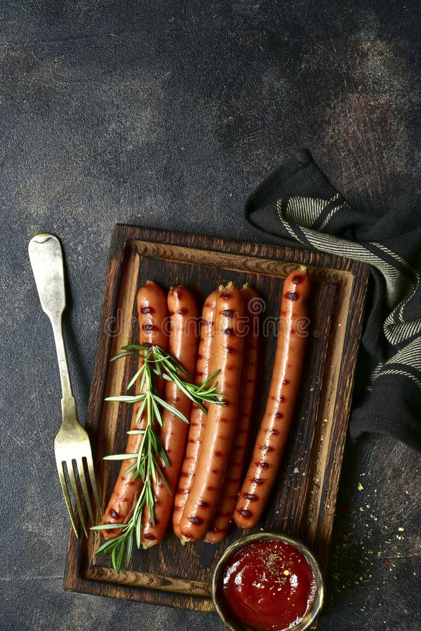 Traditional bavarian sausage with ketchup. Top view with copy space. Traditional bavarian sausage with ketchup on a wooden cutting board. Top view with copy royalty free stock photos