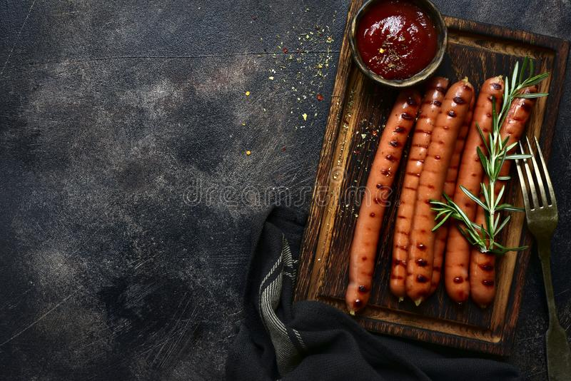 Traditional bavarian sausage with ketchup. Top view with copy space. Traditional bavarian sausage with ketchup on a wooden cutting board. Top view with copy royalty free stock photo