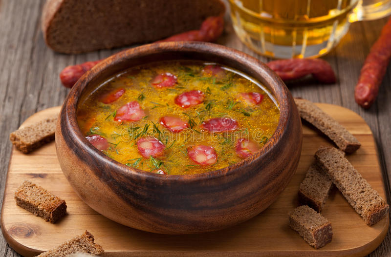 Traditional beer soup with cheese sausage dill. Croutons and beer on vintage background stock images