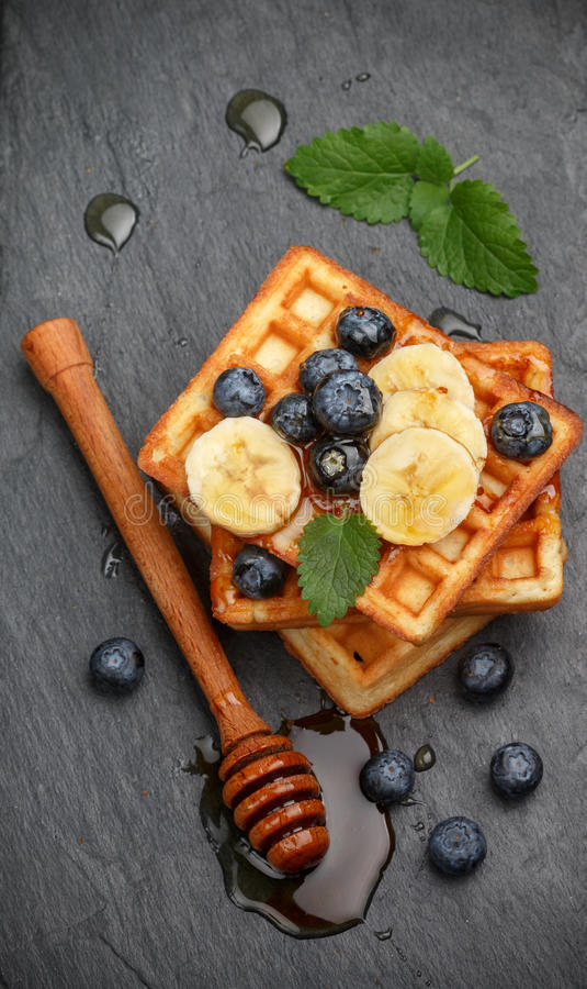 Traditional Belgian waffles with blueberries, banana and honey. On a black slate plate. Gourmet Breakfast. Selective focus royalty free stock image