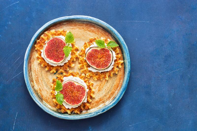 Traditional Belgian waffles with cream, figs and mint leaves on a blue rustic background. Top view, copy space. royalty free stock image