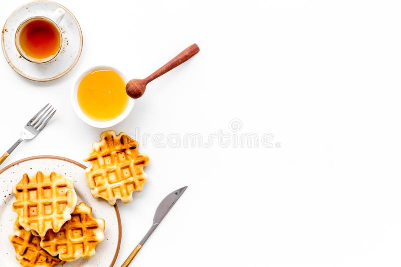 Traditional belgian waffles with honey and tea on served white table background top view mockup. Hot homemade breakfast. Traditional belgian waffles with honey stock photo