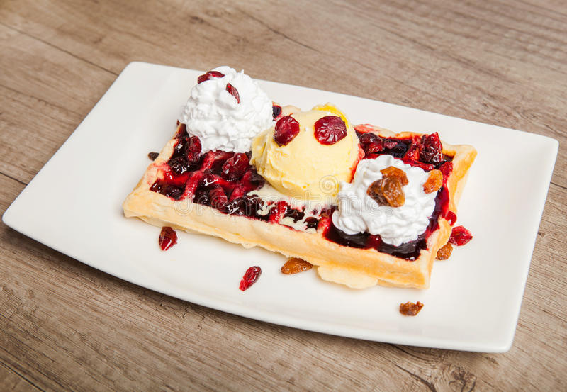 Traditional Belgian waffles with ice cream and berry fruit sauce royalty free stock image