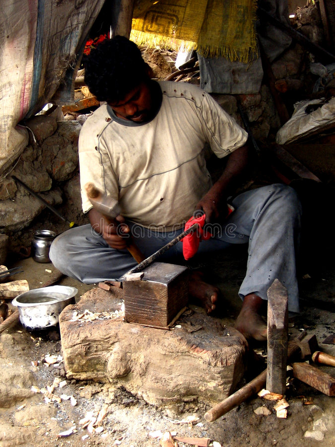 Traditional Blacksmith. A traditional blacksmith from india shapes up a hot iron royalty free stock photography