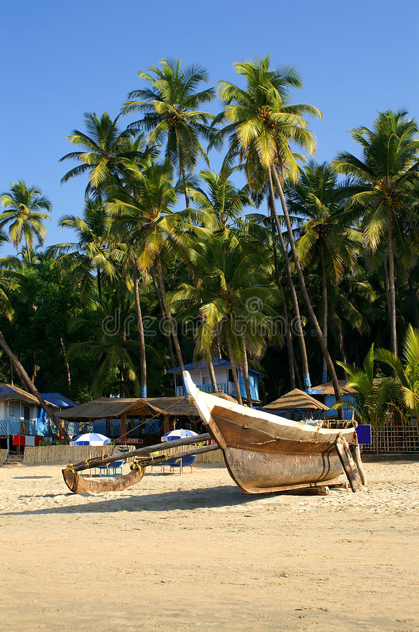 Traditional boat and bungalows. At the tropical beach of Palolem, Goa state, India stock images
